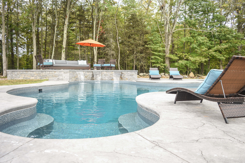 This is a photo of a custom in-ground swimming pool with chairs around it.