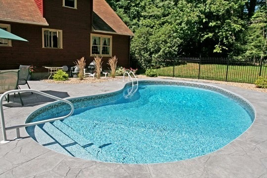 This is a photo of a custom kidney inground pool with black fence and stairs installed by Julianos