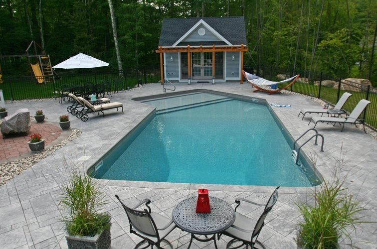 This Is A Photo Of A Lazy L Style Inground Swimming Pool With Custom Pool House And Pool Furniture.