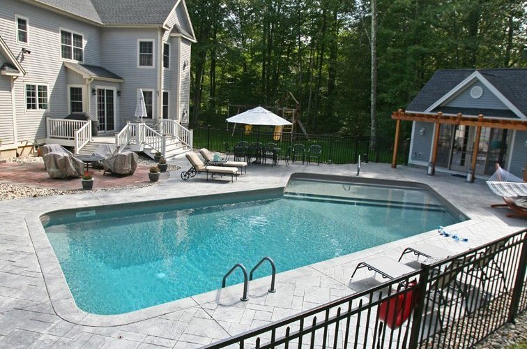 This Is A Photo Of A Lazy L Style Inground Swimming Pool With Custom Pool House And Furniture.