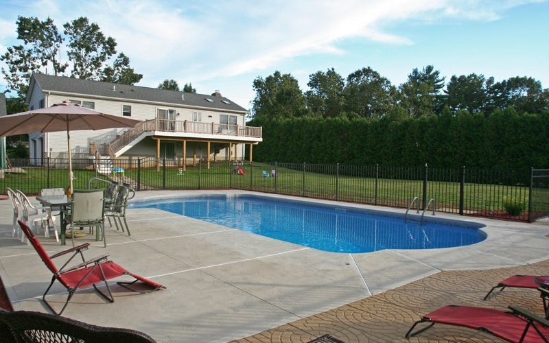 This Is A Photo Of A Roman In Ground Pool In Somers, CT With Custom Pavers, Black Fence And Steps.
