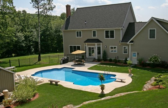 This Is A Photo Of A Roman In Ground Pool In Tolland, CT With Custom Pavers, Diving Board And Steps.