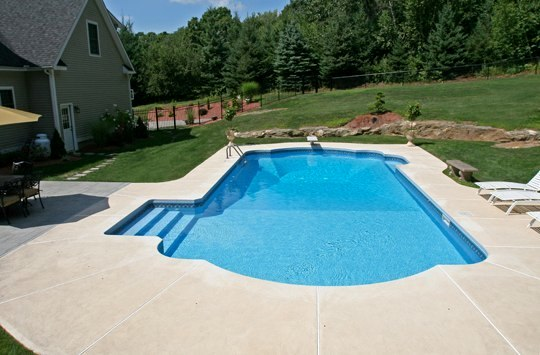This Is A Photo Of A Roman In Ground Pool In Tolland, CT With Custom Pavers, And Steps.
