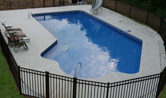This Is A Photo Of A Lazy L Style Custom Inground Swimming Pool With A Black Fence And Water Slide.