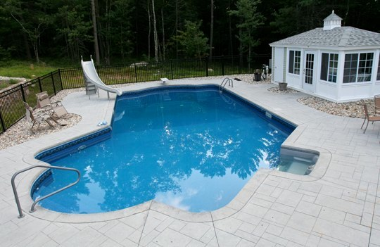 This Is A Photo Of A Lazy L Style Custom Inground Swimming Pool With A Custom Pool House And Water Slide.