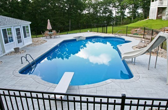 This Is A Photo Of A Lazy L Style Custom Inground Swimming Pool With A Custom Pool House, Water Slide. And Diving Board.