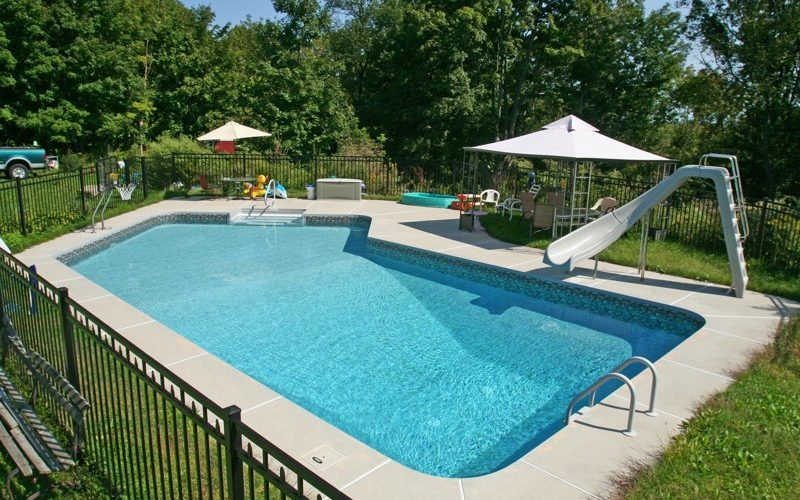 This Is A Photo Of A Lazy L Style Custom Inground Swimming Pool With A Black Fence, Steps And Water Slide.
