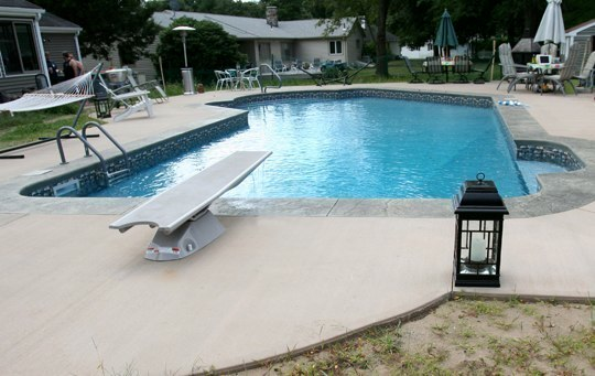 This Is A Photo Of A Lazy L Style Custom Inground Swimming Pool With A Black Steps And Diving Board.