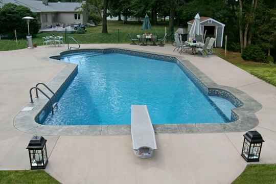 This Is A Photo Of A Lazy L Style Custom Inground Swimming Pool With A Black Fence, Steps And Diving Board.