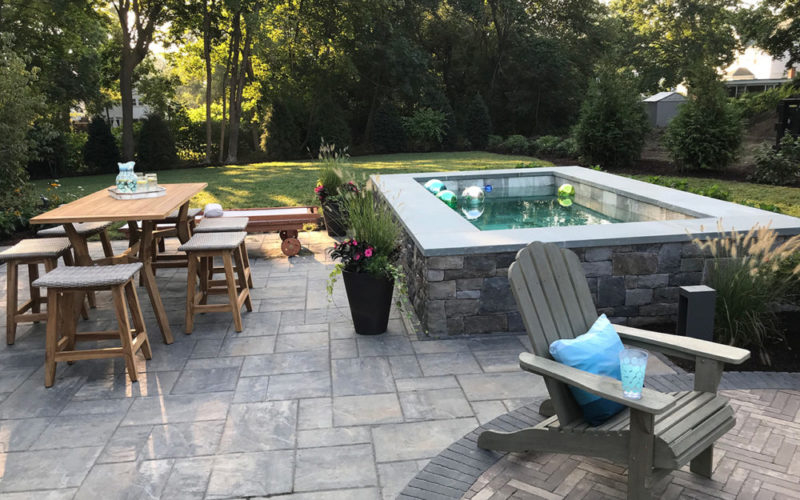 This Is A Picture Of Soake Pool Built Out Of Stone On A Stone Patio.