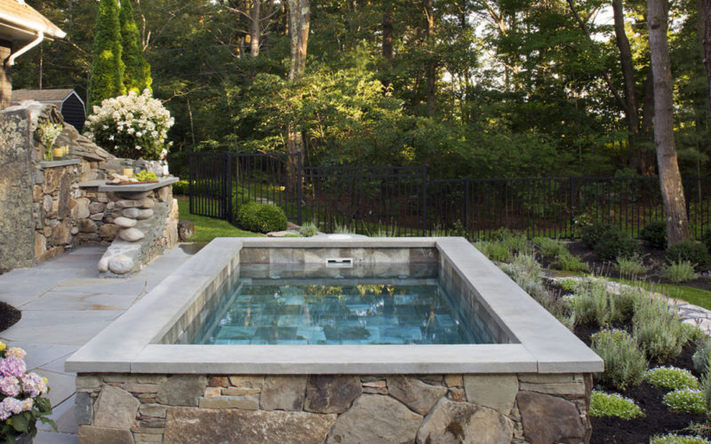 This Is A Picture Of Soake Pool Built Out Of Stone On A Stone Patio In A Backyard.