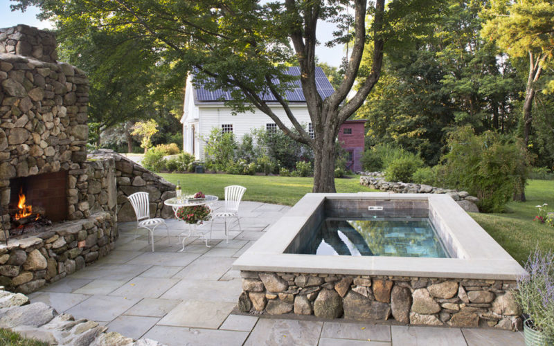 This Is A Picture Of Soake Pool Built Out Of Stone In A Backyard Patio, And Fireplace.