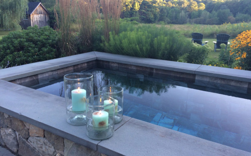 This Is A Picture Of Soake Pool Built Out Of Stone With Candles On The Coping In A Backyard.