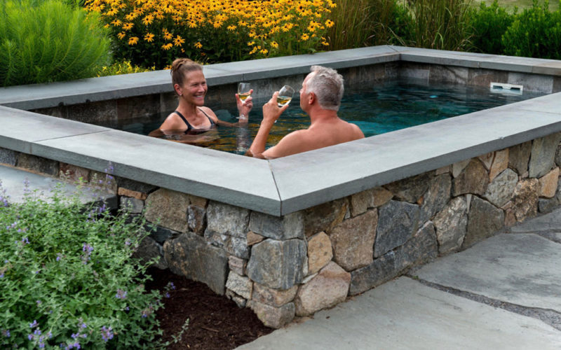 This Is A Picture Two People Enjoying Their Soake Pool With Glasses Of Wine.