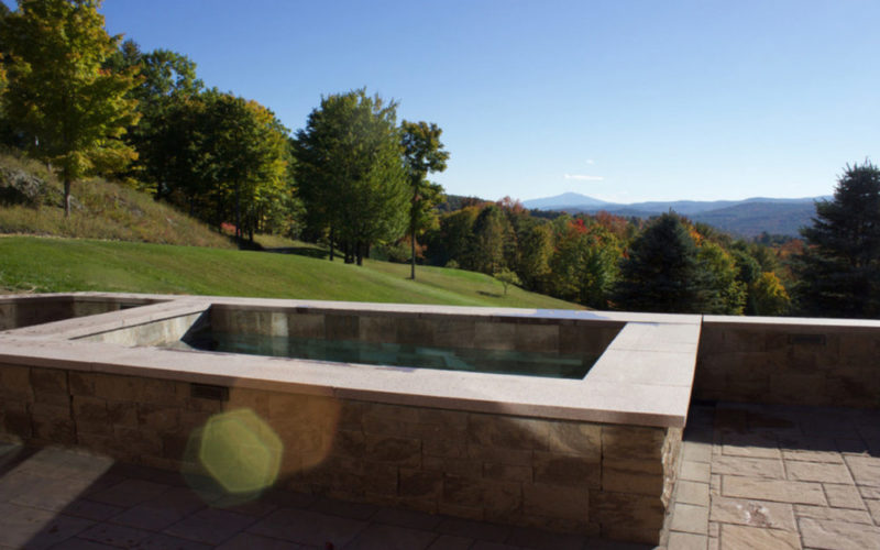 This Is A Photo Of A Stone Soake Pool Overlooking A Spacious Backyard And Mountain Range.