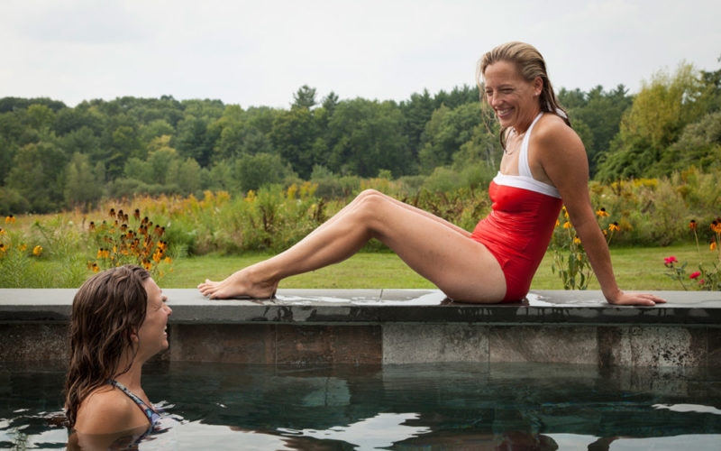 This Is A Photo Of Two Women Enjoying Their Stone Soake Pool Overlooking A Forest.