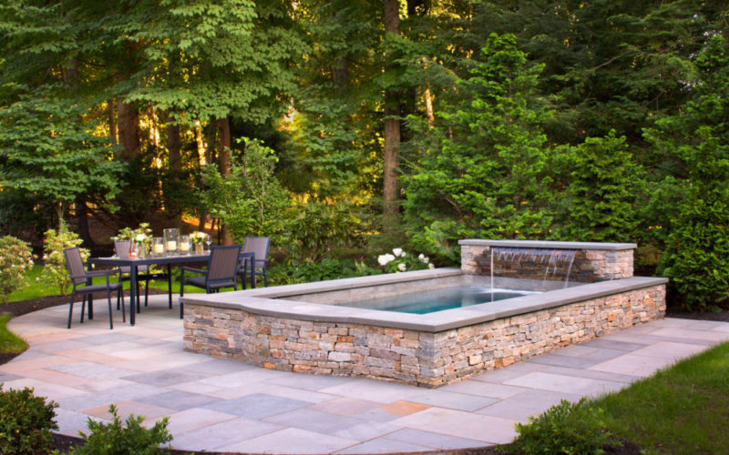This Is A Picture Of Soake Pool Built Out Of Stone With A Flowing Spout In A Backyard.