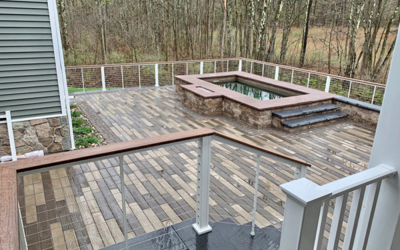 This Is A Photo Of A Stone Soake Pool Overlooking A Forest On A Wooden Deck.
